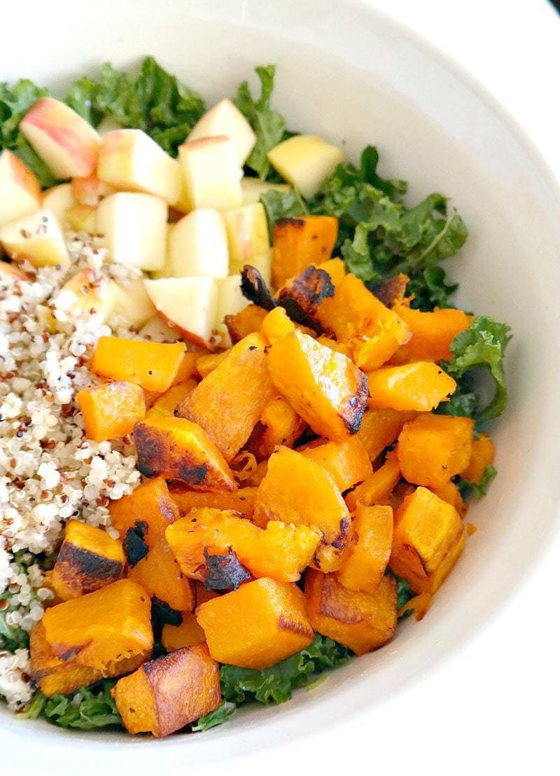Harvest Kale and Quinoa Butternut Squash Salad. Vegan and Gluten Free with a Oil-Free Champagne Vinaigrette. Roasted butternut squash, crisp apple, nourishing quinoa, kale and raisins for a hint of sweetness. A lean, clean & green fall recipe that's perfect for Thanksgiving or any holiday party. #vegan #fall #autumn #salad