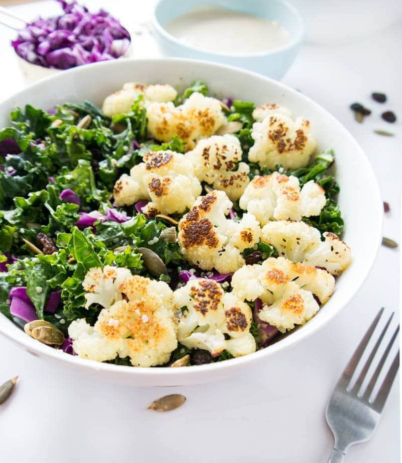Kale and Roasted Cauliflower Salad. Vegan & Gluten Free. Simple, light, filling and warming with raisins, pumpkin seeds, hemp seeds & the creamiest lemon tahini dressing. #vegan #kale #salad #cauliflower