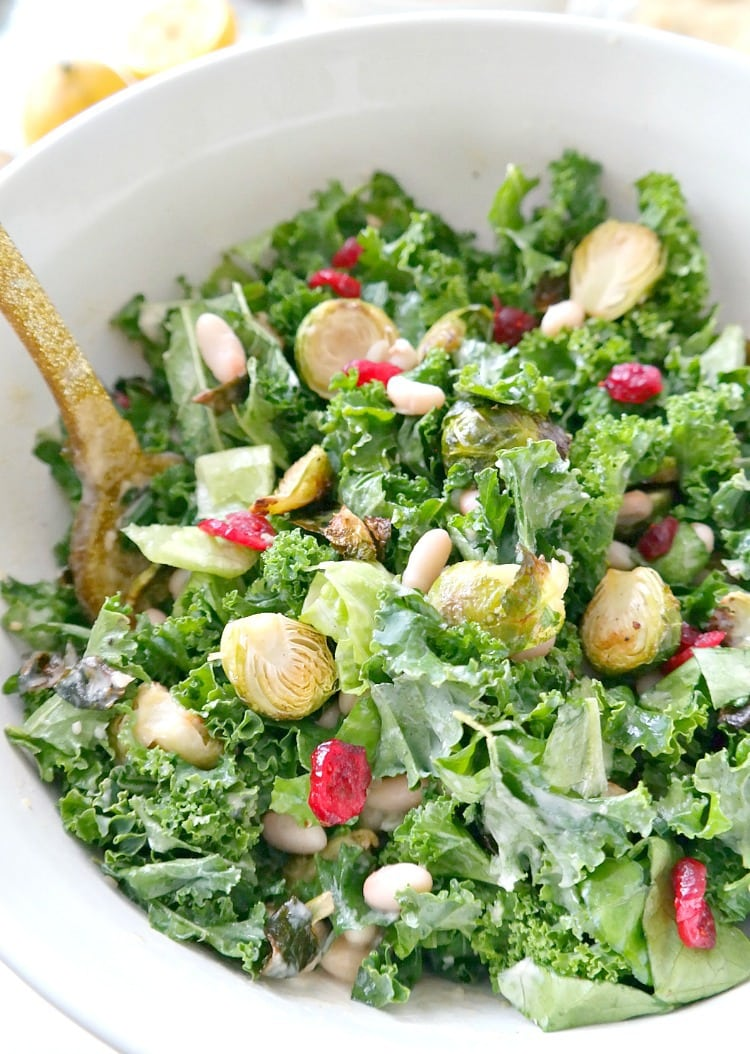 Holiday Kale & Cranberry Vegan Salad. A crowd-pleasing holiday favorite! Curly kale, crispy brussels sprouts, sweet cranberries and a delectably creamy tahini dressing with a lemony kick. From The Glowing Fridge