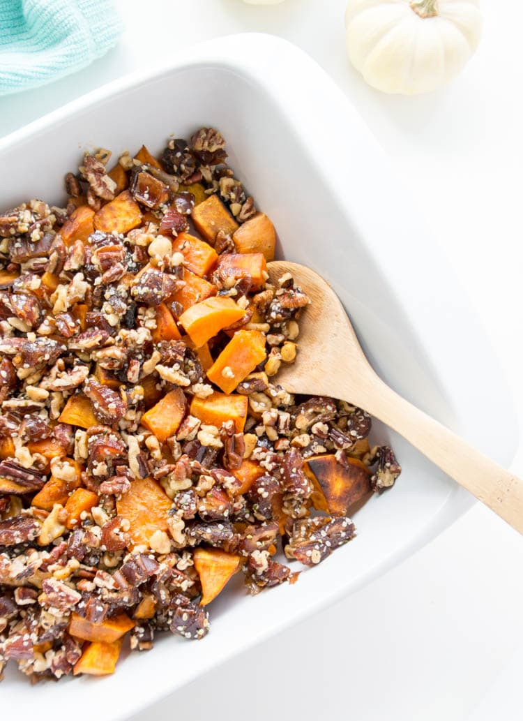 Roasted Sweet Potatoes with Maple Pecan Date Crumble. Vegan and Gluten Free! Melt in your mouth (yet crispy) sweet potatoes with a sticky, gooey and decadent crumble of pecans, walnuts, dates, maple syrup and cinnamon. This will be the highlight sweet potato side for Thanksgiving or any holiday! #vegan #sweetpotatoes #thanksgiving