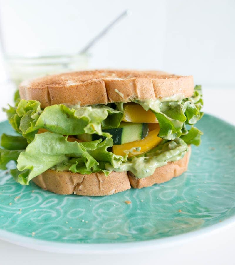 Spicy Avocado Ranch Cucumber Sandwich. Vegan, Gluten Free bread option. The creamiest, cooling Spicy Avocado Ranch with crunchy cucumber and heirloom tomato on toasted bread. The best fresh, summer lunch! From The Glowing Fridge #vegan #avocadoranch #sandwich