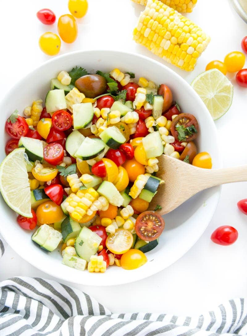 Summer Glow Salad. Super fresh and seasonal for summer with mini tomatoes, fresh corn and crisp cucumber with all the lime juice. Makes a perfect appetizer paired with tortilla chips and hummus, a side dish or served over kale and quinoa for lunch! #vegan #summer #glow #salad