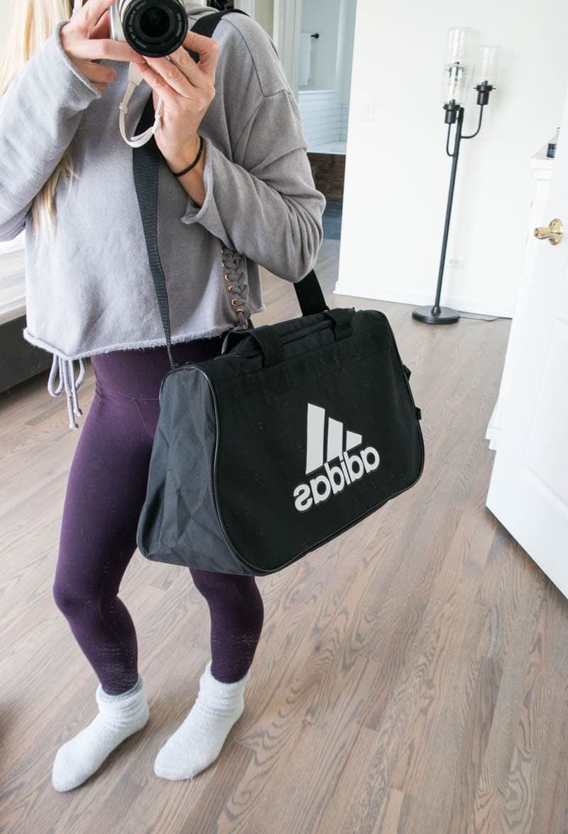 A Peek Inside My Gym Bag. My gym essentials including booty bands, sliders, training shoes, alkaline water, vegan protein snack bars, best gym duffle bag and more! #gymbag #gymessentials